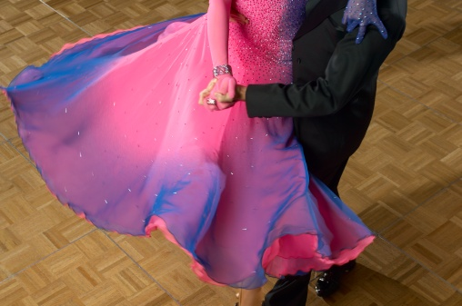 A man in a suit spinning a woman wearing a ball gown on a dance floor